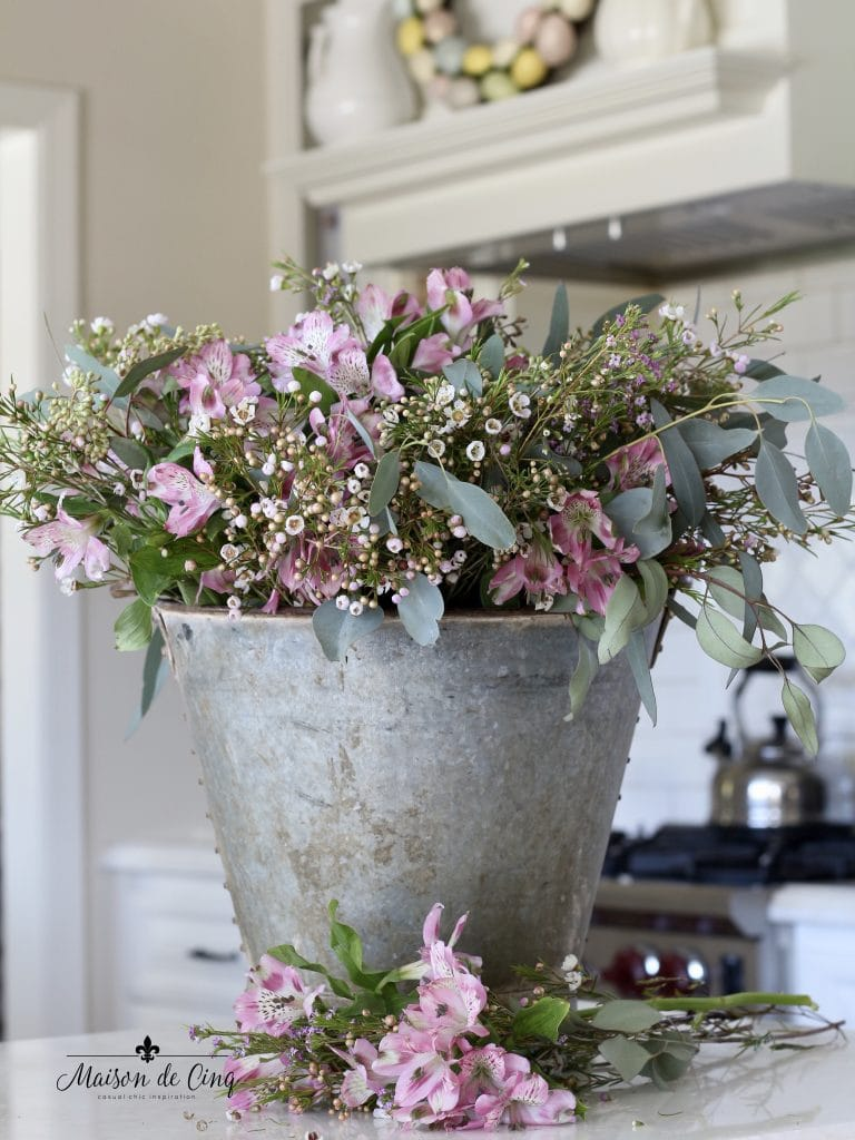 Easter decorating pink spring flowers in vintage rustic bucket white farmhouse kitchen