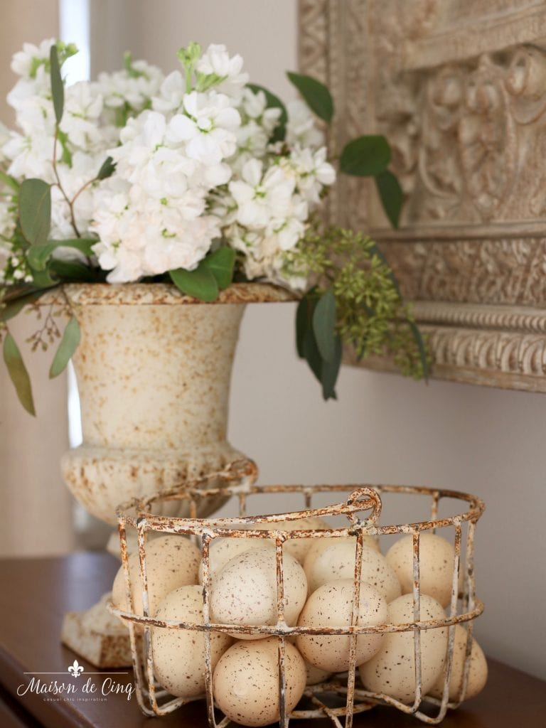 Easter decorating white flowers in vintage urn easter eggs in basket spring vignette french country