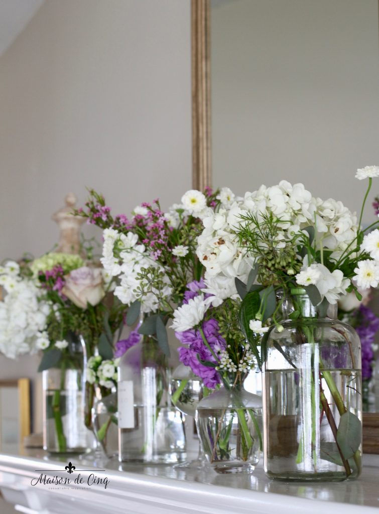 simple spring mantel purple and white flowers in glass vases