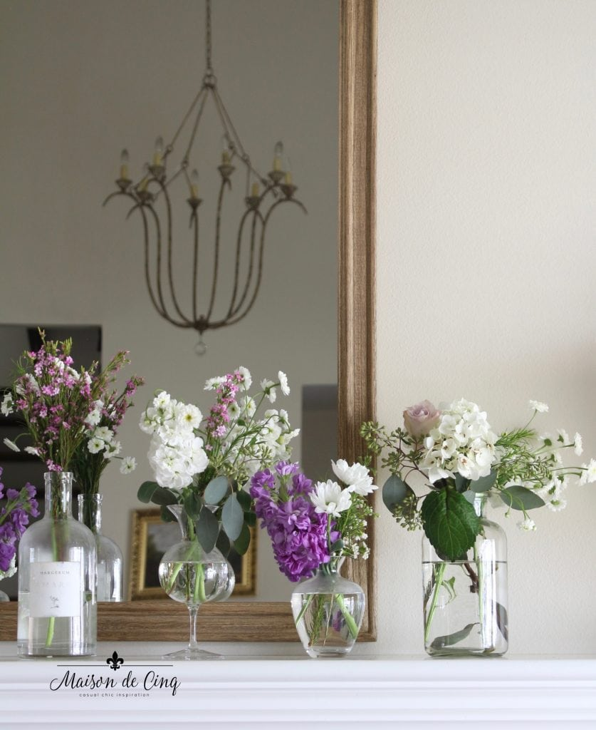 simple spring mantel with purple and white flowers in glass vases display spring decor