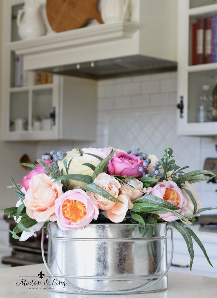 spring decorating roses and greens in bucket in white french country kitchen