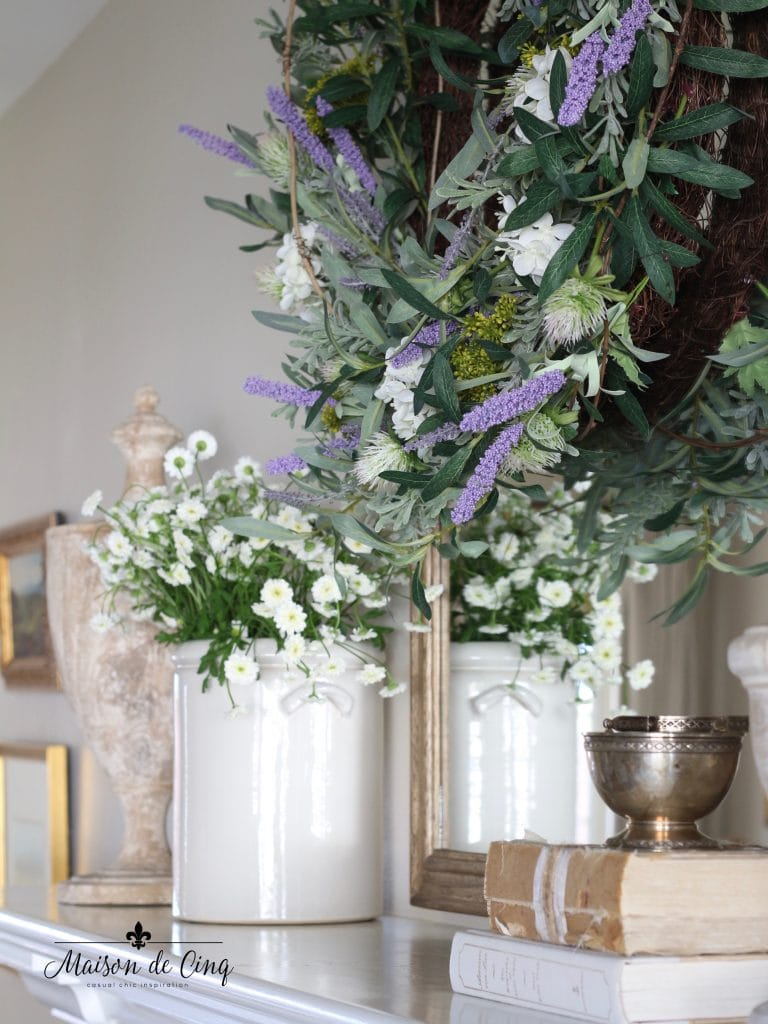 spring decorating white flowers in pot, lavender wreath and urns on mantel