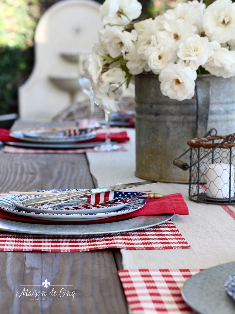 patriotic table setting with white roses on backyard table red white and blue