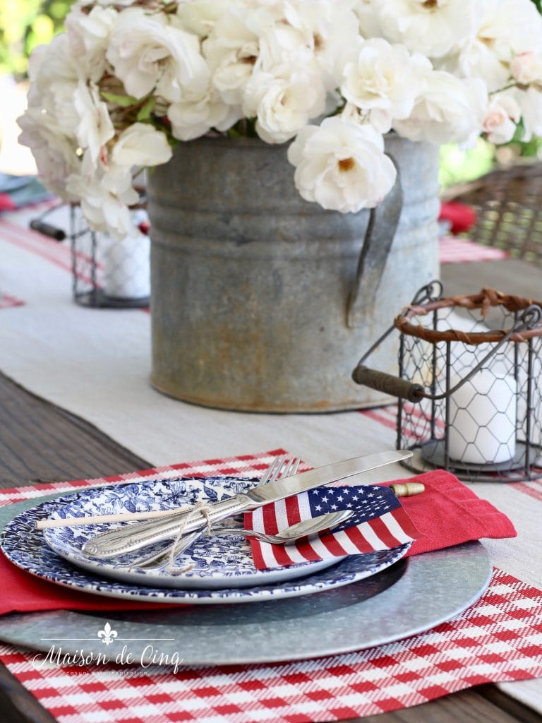 patriotic table setting red napkin and flag on blue floral plate