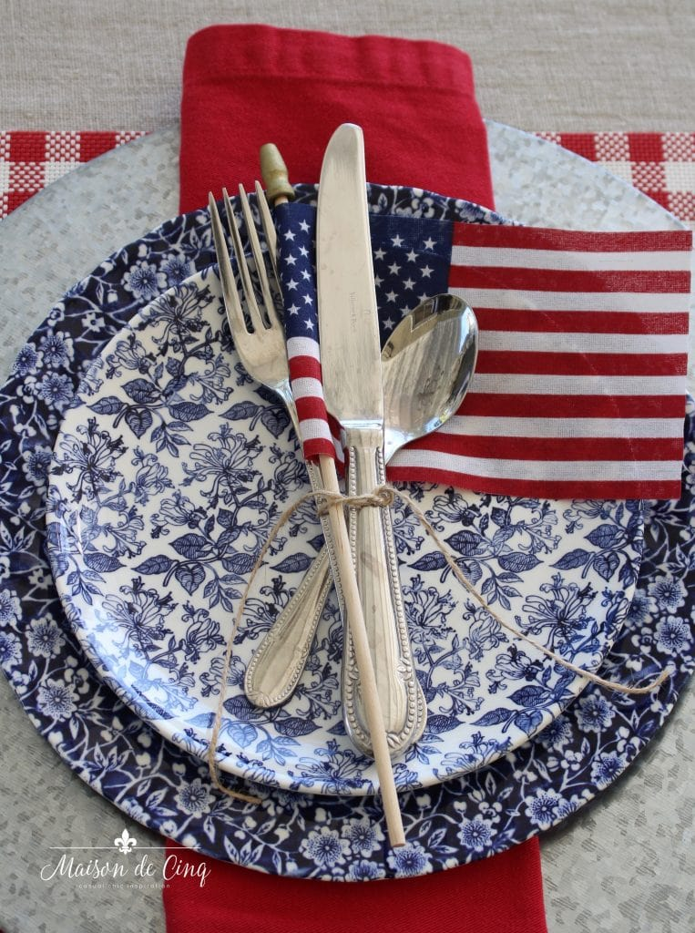 patriotic table setting blue floral plates with american flag and red napkin