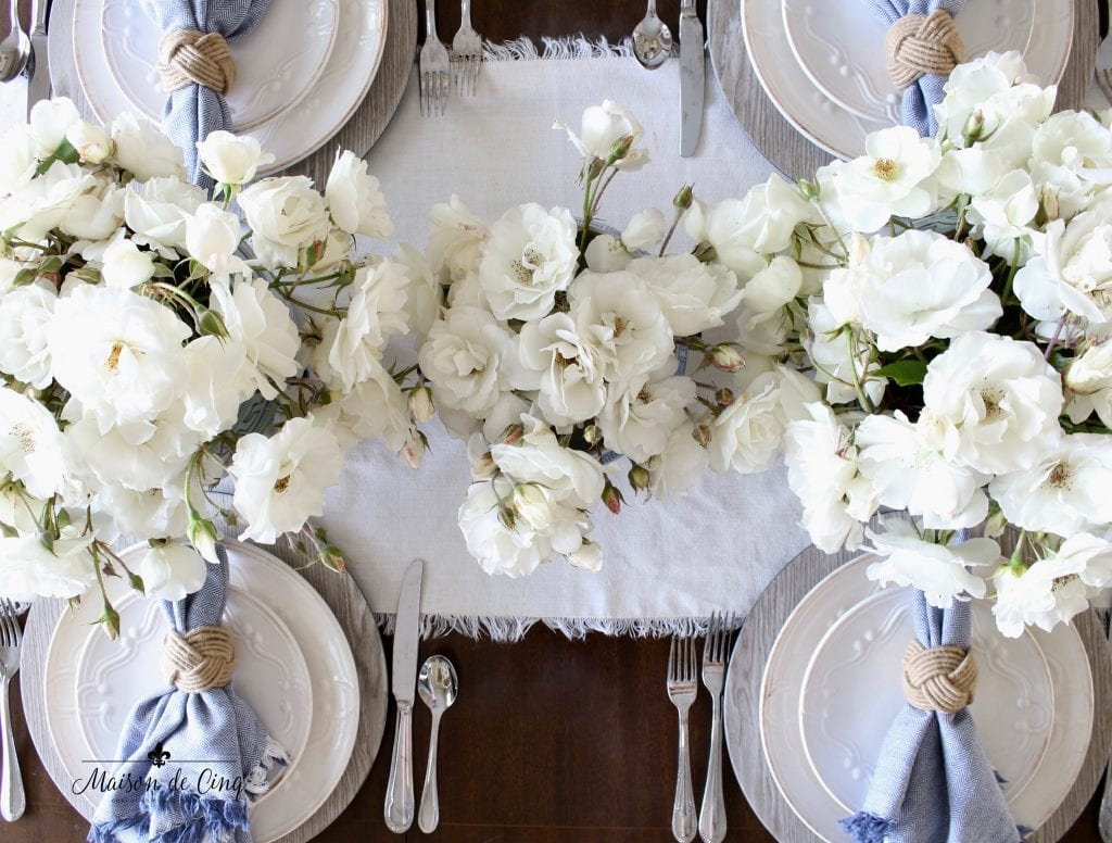 summer table setting gorgeous white roses centerpiece with blue and white napkins