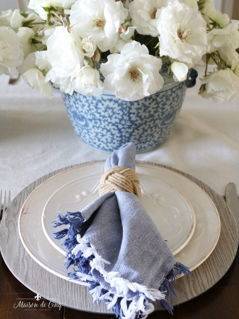 summer table setting blue and white napkin white roses wood charger