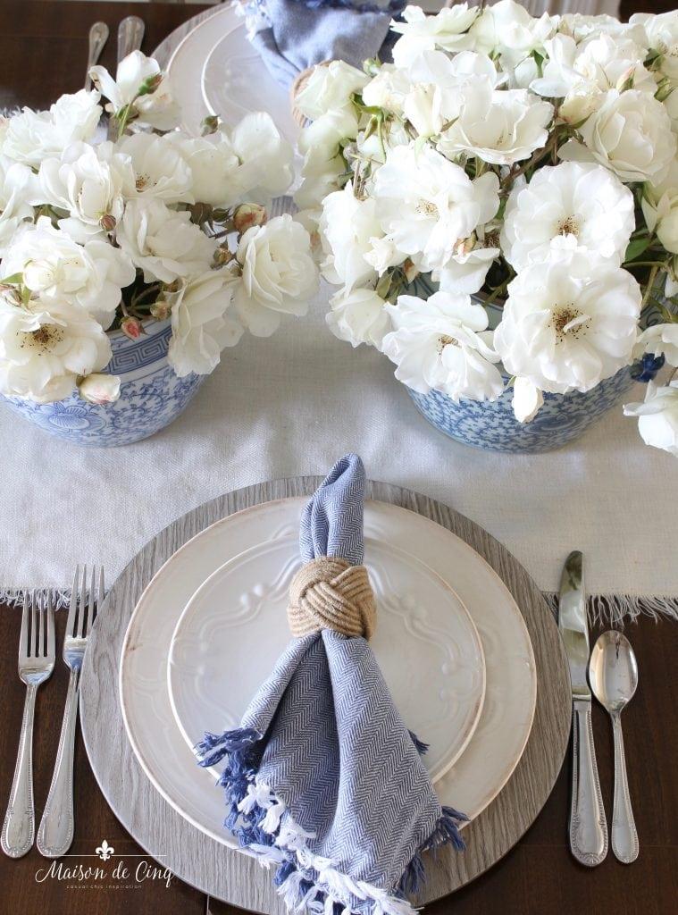 summer table setting blue and white napkin linen runner white roses centerpiece