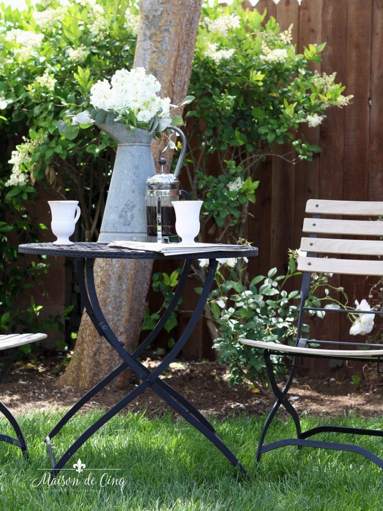 landscape remodel reveal chairs and table with flowers and coffee in yard