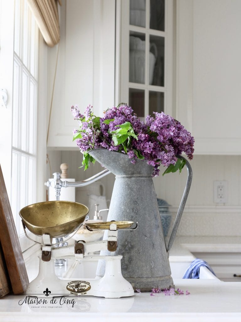 simple summer decorating lilacs in french zinc pitcher with vintage scale in white farmhouse kitchen