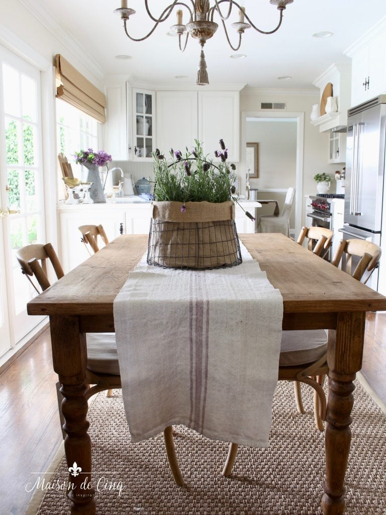 simple summer decorating french farmhouse kitchen with lavender in metal basket on farmhouse table
