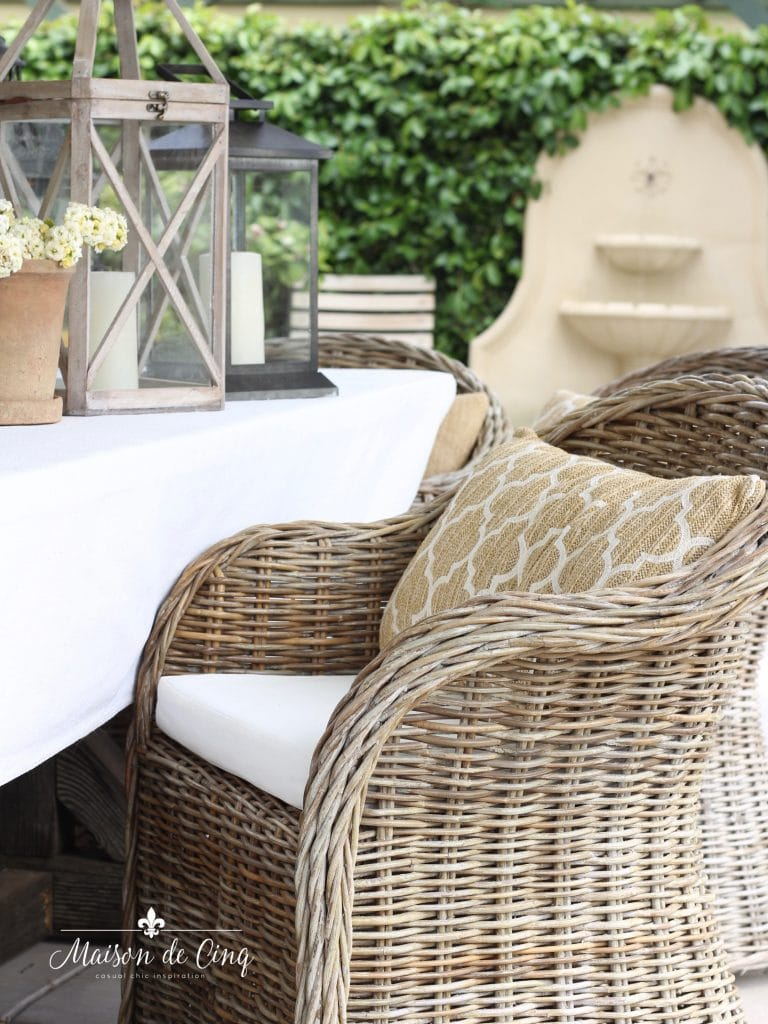 casual chic summer entertaining on the patio wicker chairs lanterns fountain