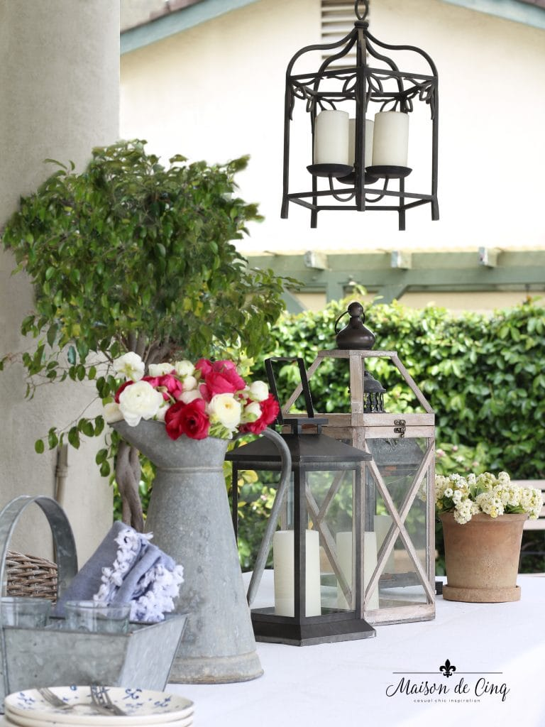 summer entertaining outdoors on patio with lanterns and flowers