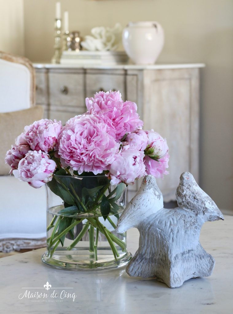 summer decorating ideas pink peonies in glass vase bird statue