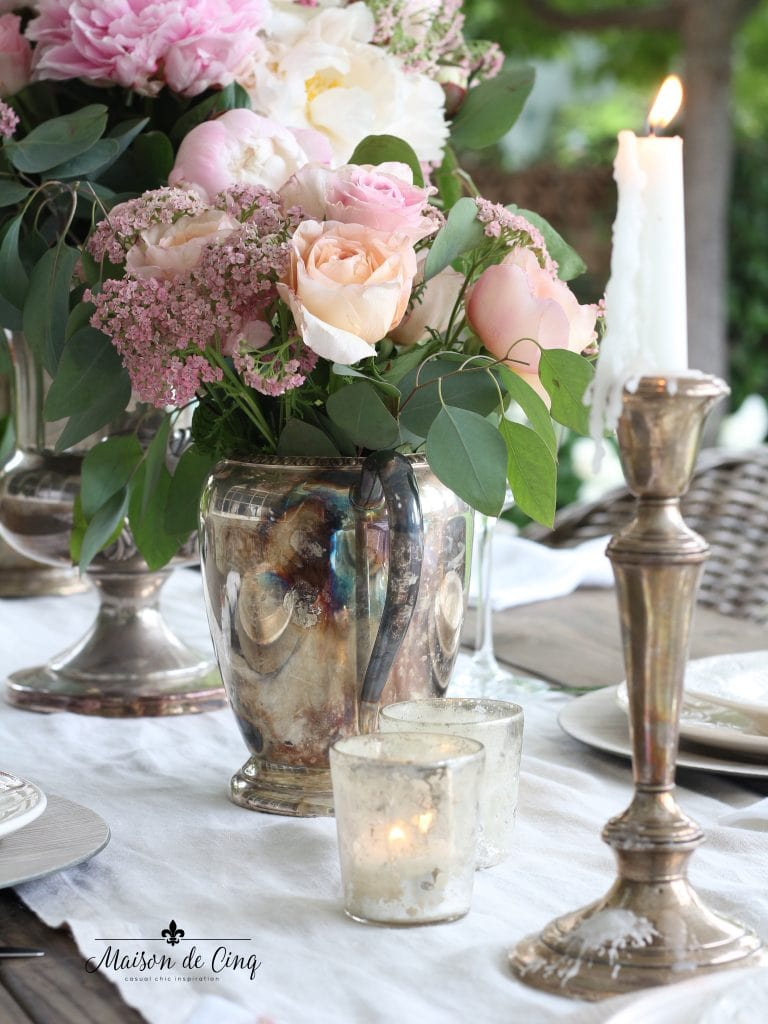 romantic summer tablescape with pink roses and silver candlesticks on linen runner