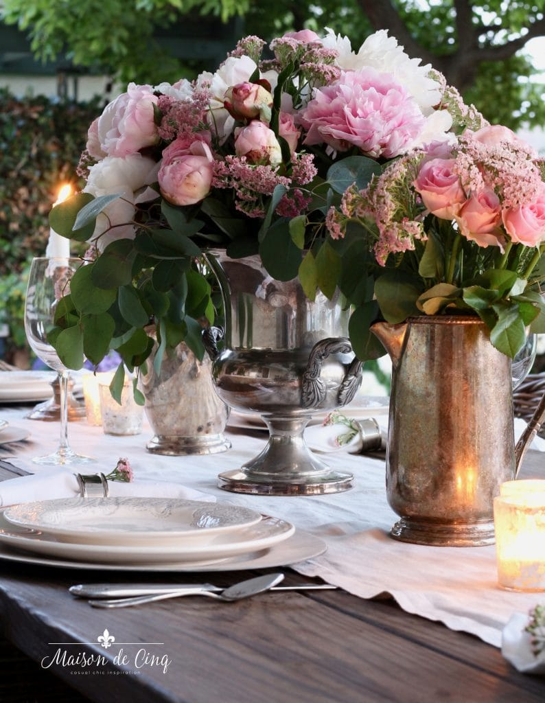 summer tablescape featuring pink peonies and roses in vintage silver pitchers