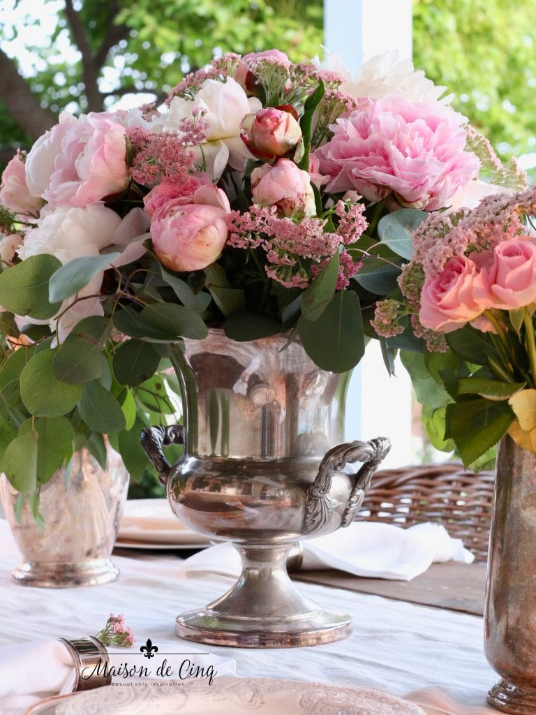 romantic summer table setting pink roses and peonies in antique silver champagne bucket summer inspiration