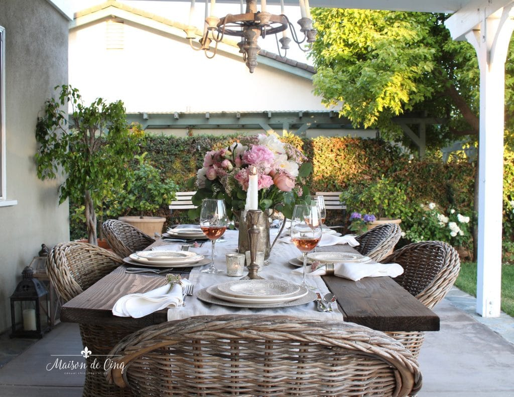 romantic summer table setting backyard patio wicker chairs farmhouse table