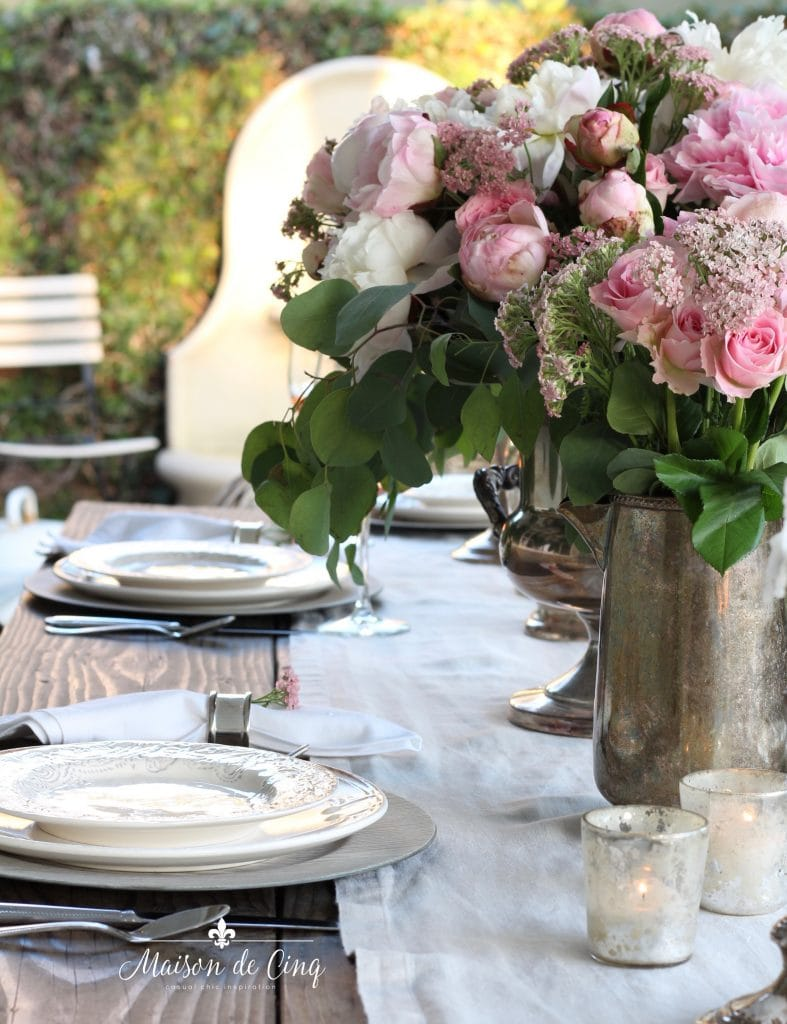 romantic summer table setting in backyard with pink peonies and roses outdoor dining