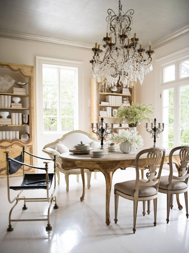 mixing dining chairs around French country table crystal chandelier dining room decor