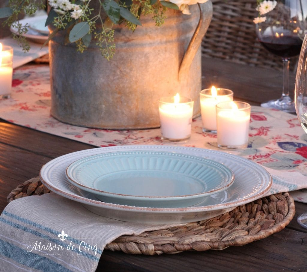 mint green plate over rattan charger and votive candles