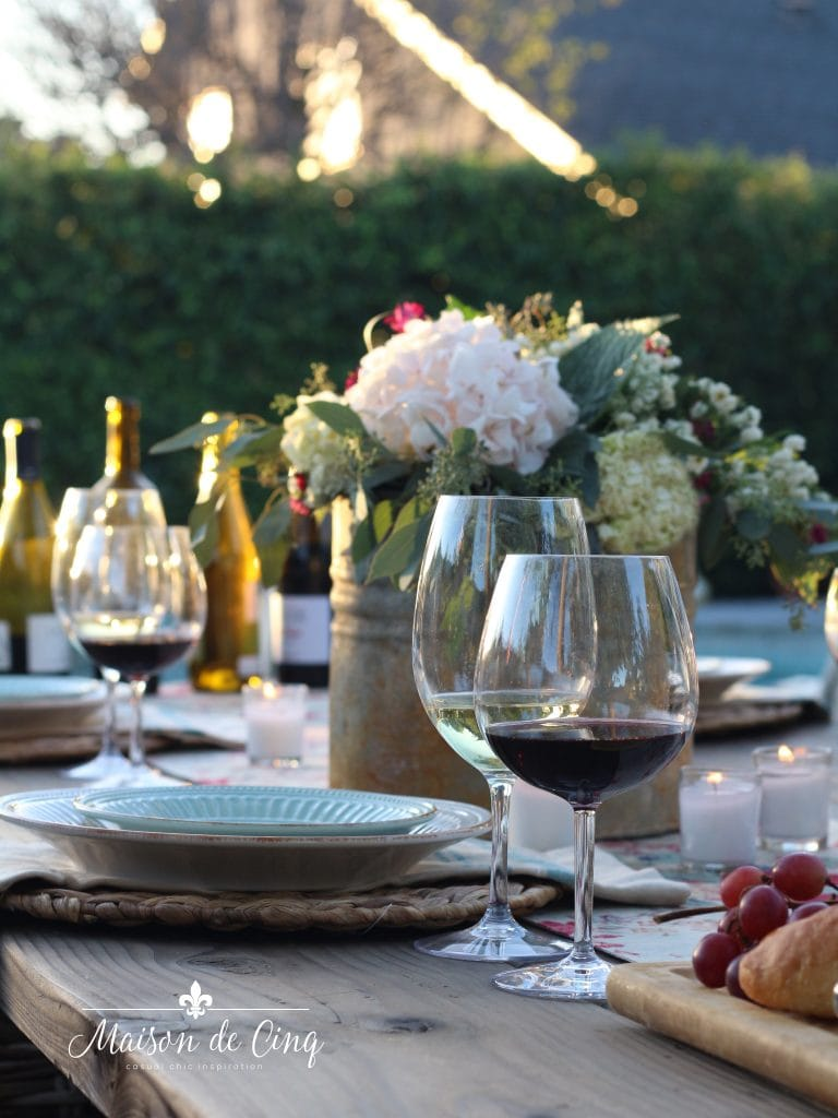 summer tablescape with wine and floral centerpiece