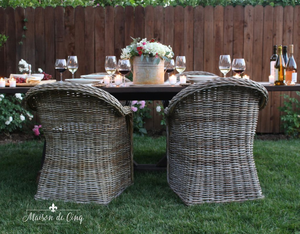 summer wine and cheese party in the garden farmhouse table wicker chairs