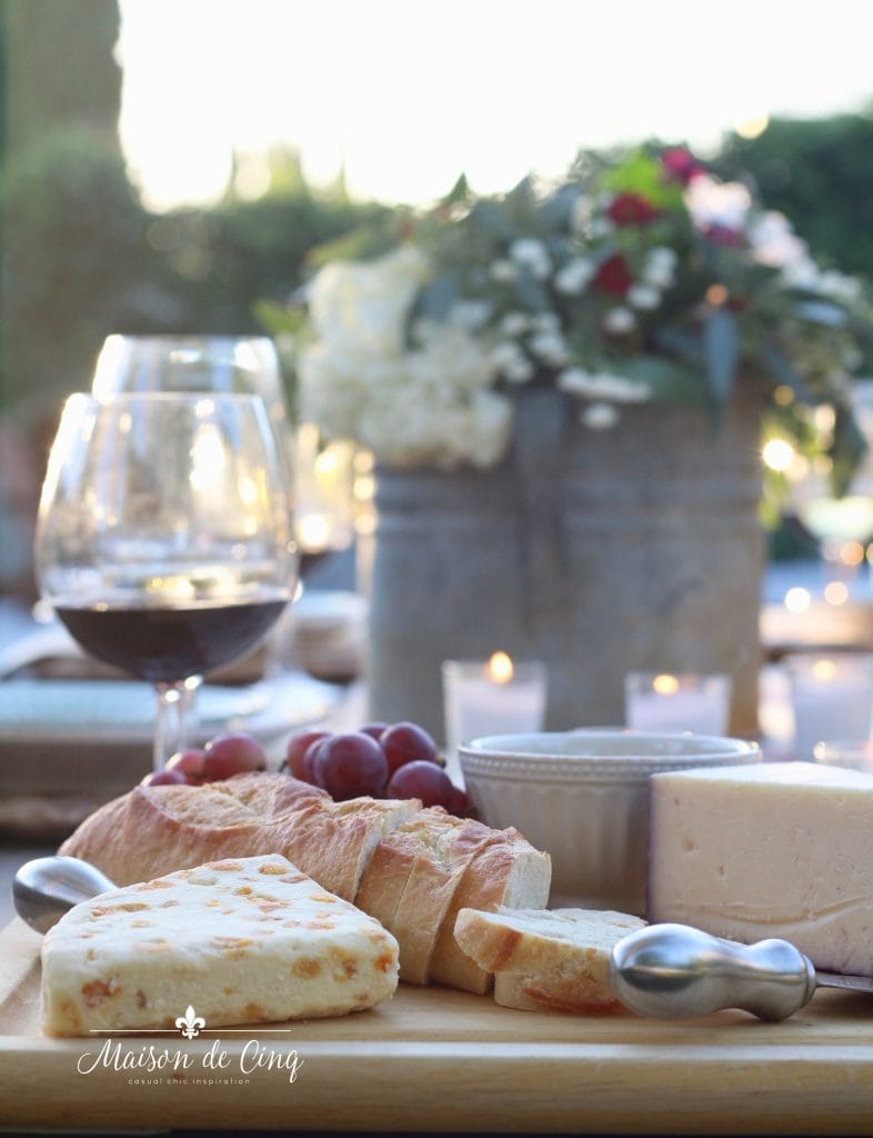 wine and cheese platter board with bread cheese grapes and candles