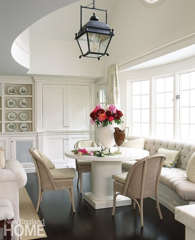 mix of wicker dining chairs with a banquette in a charming farmhouse breakfast area