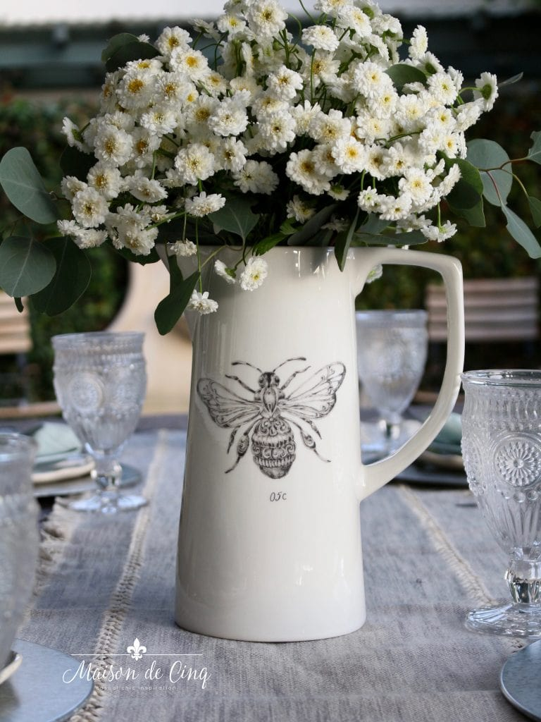 white flowers in simple white farmhouse pitcher with bee motif