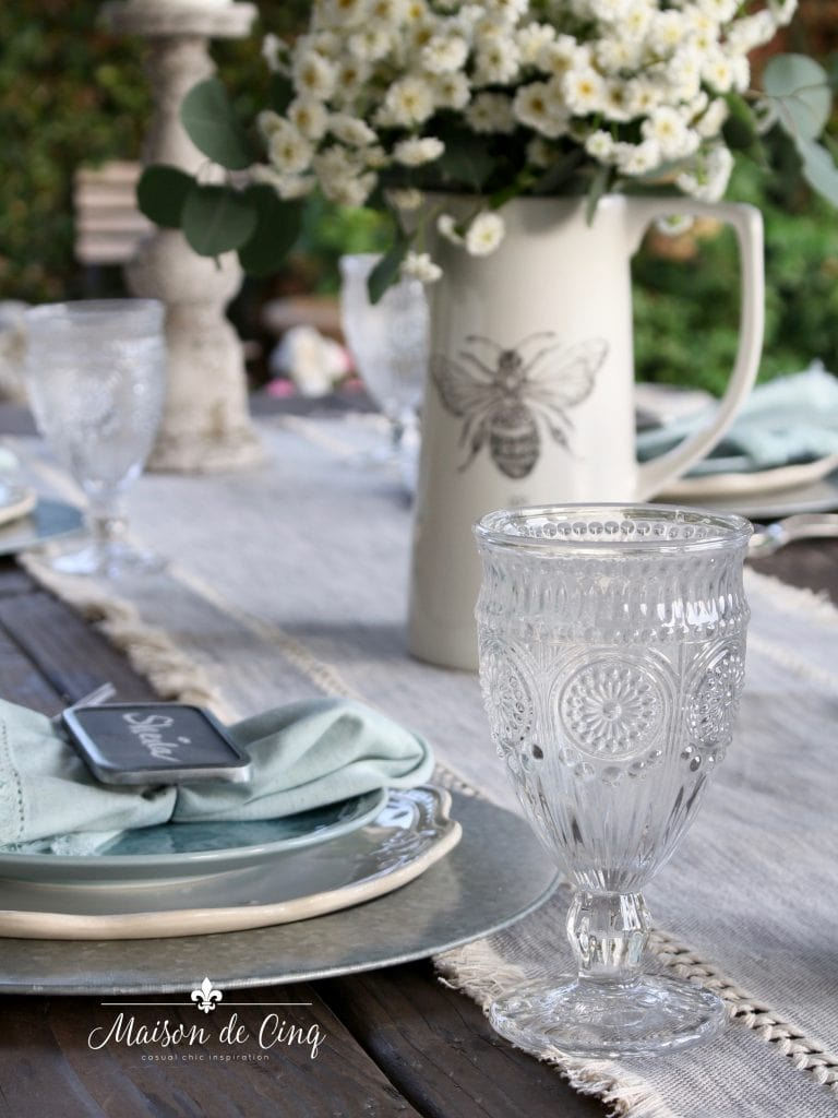 simple summer farmhouse style tablescape with white flowers and blue and grey palette