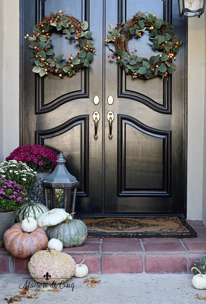 black front doors with fall wreaths and pumpkins and mums on porch