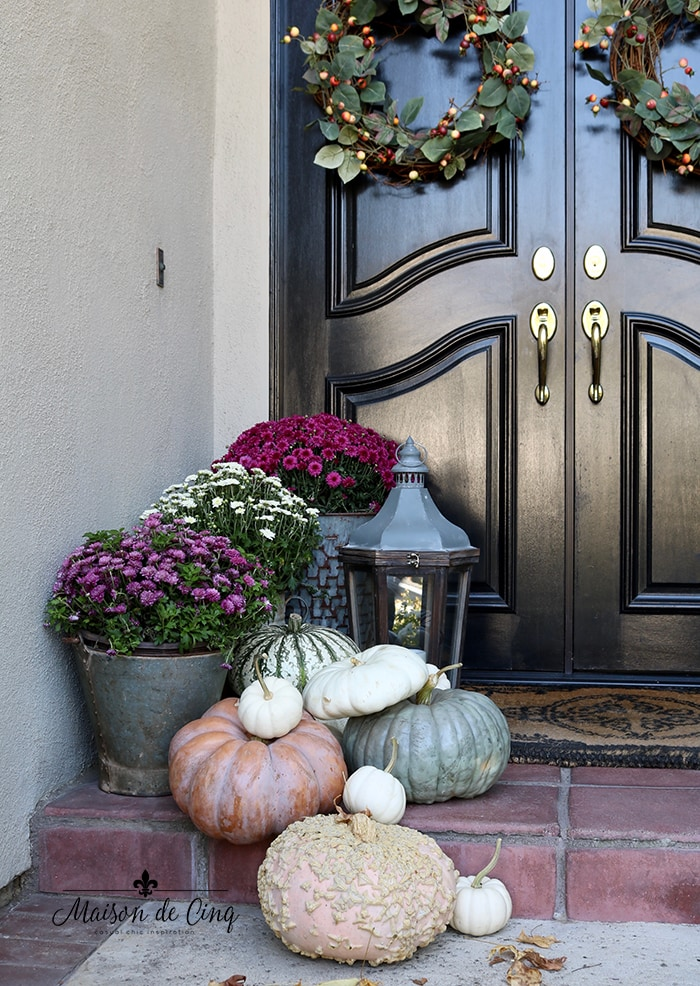 black front doors with pink mums and pumpkins fall autumn decor