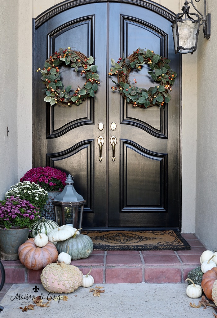 gorgeous fall porch with black doors pumpkins lanterns pink mums