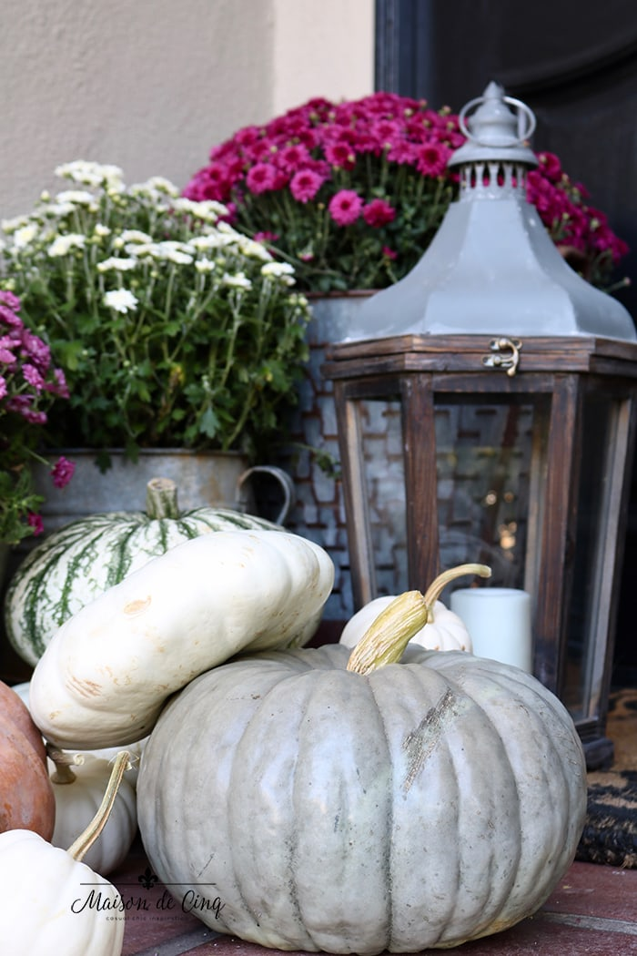 white and green pumpkins with lantern and pink mums fall porch decor