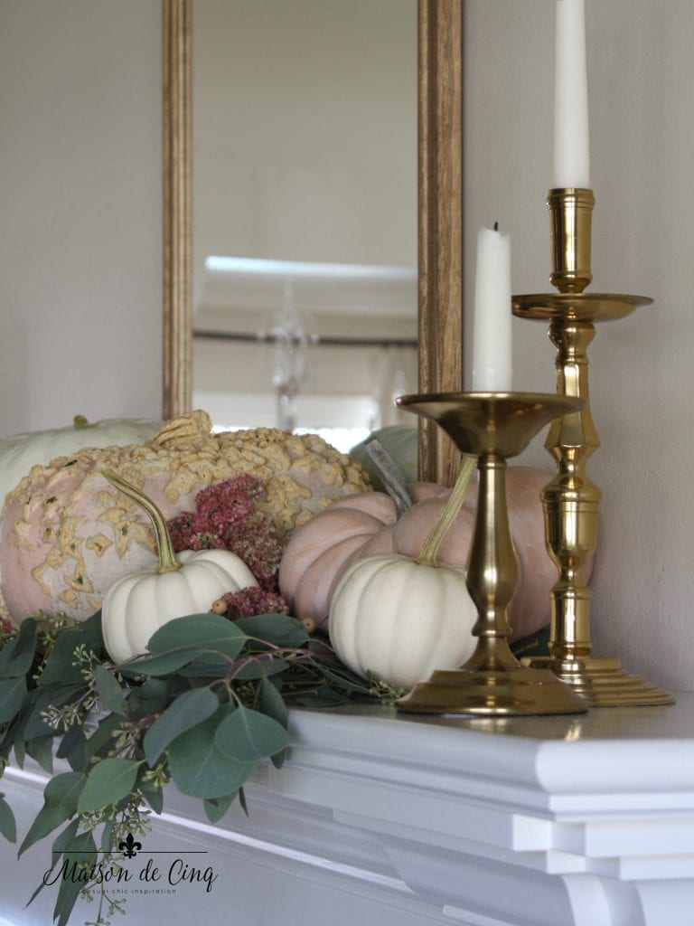 brass candleholders and pink and white pumpkins fall mantel decor