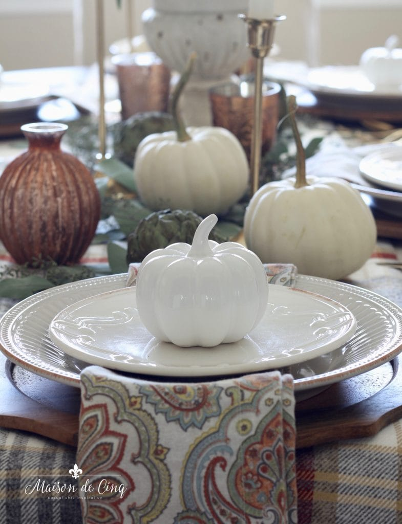 fall table setting with pumpkins white plates and paisley napkins