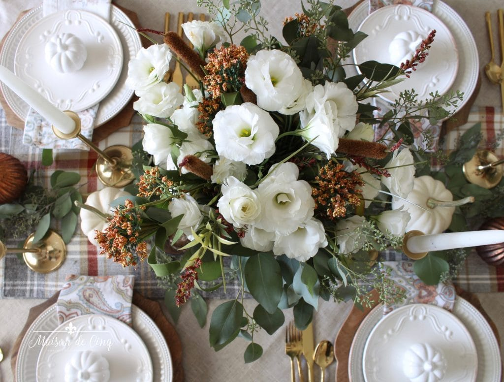 stunning fall tablescape overhead shot white flowers on plaid runner with pumpkins