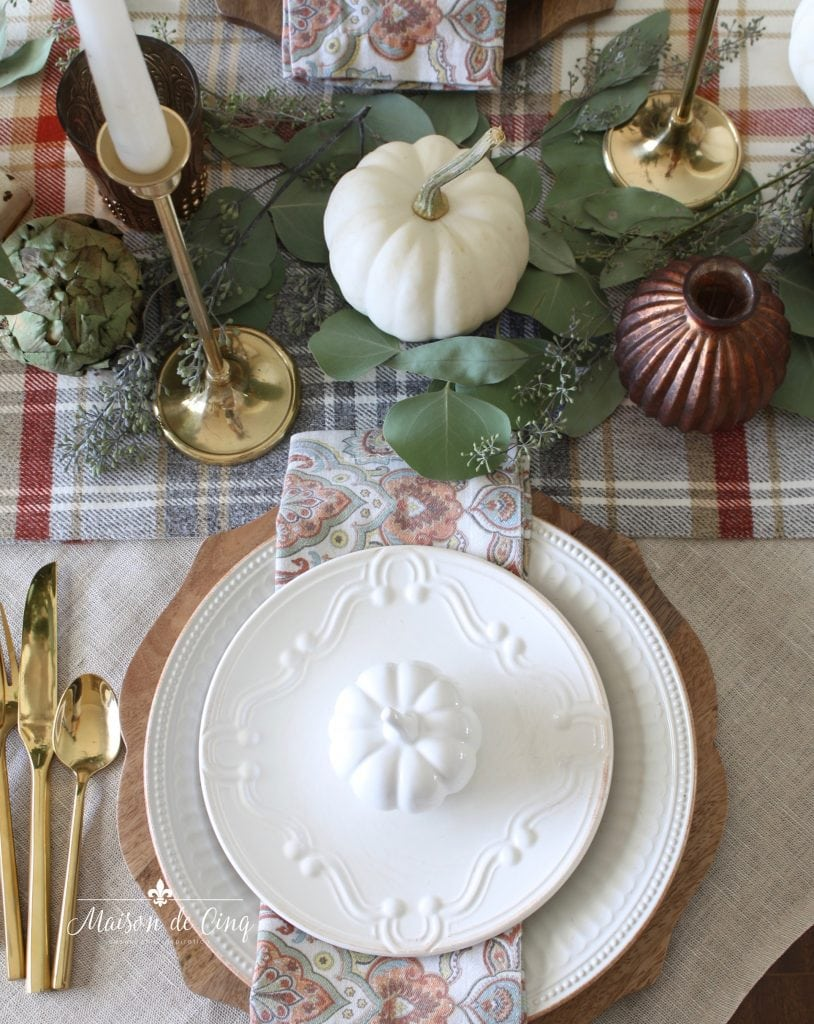 autumn tablescape white plates on wood charger with artichokes, white pumpkins, candles and greens