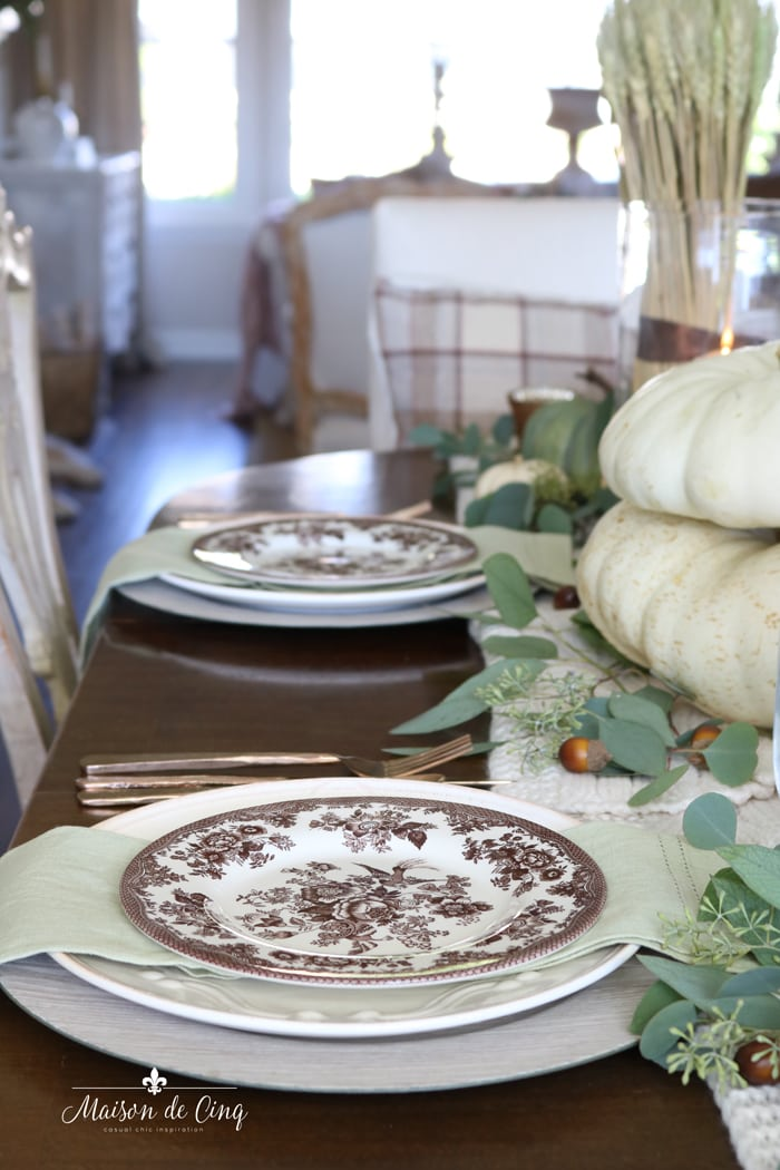 warm fall table setting with brown and green hues and white pumpkins thanksgiving tablescape