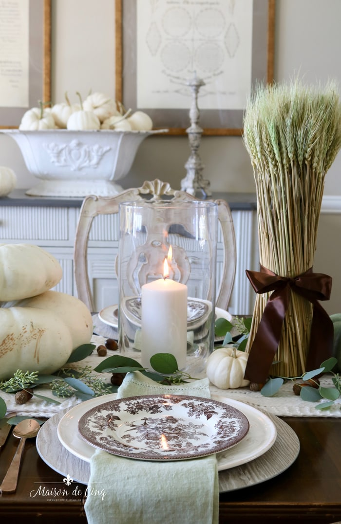 warm fall table setting in tones of green and brown white pumpkins wheat