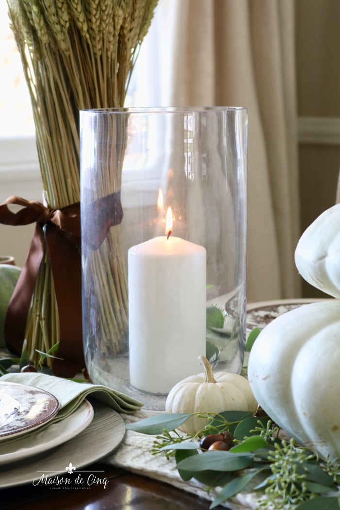 candle in hurricane with white pumpkins and wheat fall table setting ideas autumn tablescape