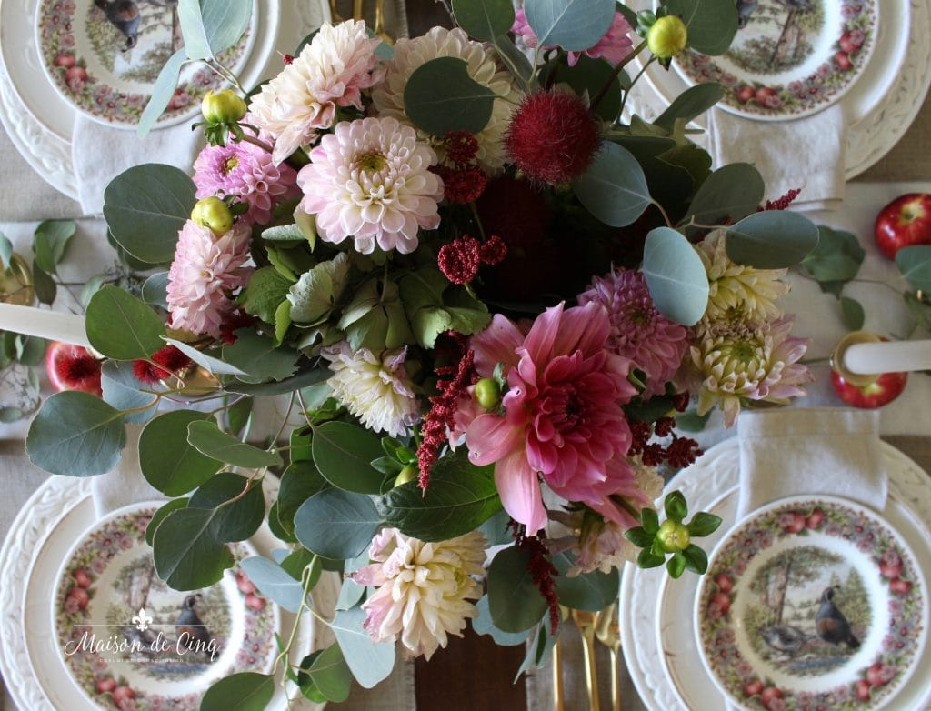 stunning fall table centerpiece with pink dahlias and eucalyptus with apples