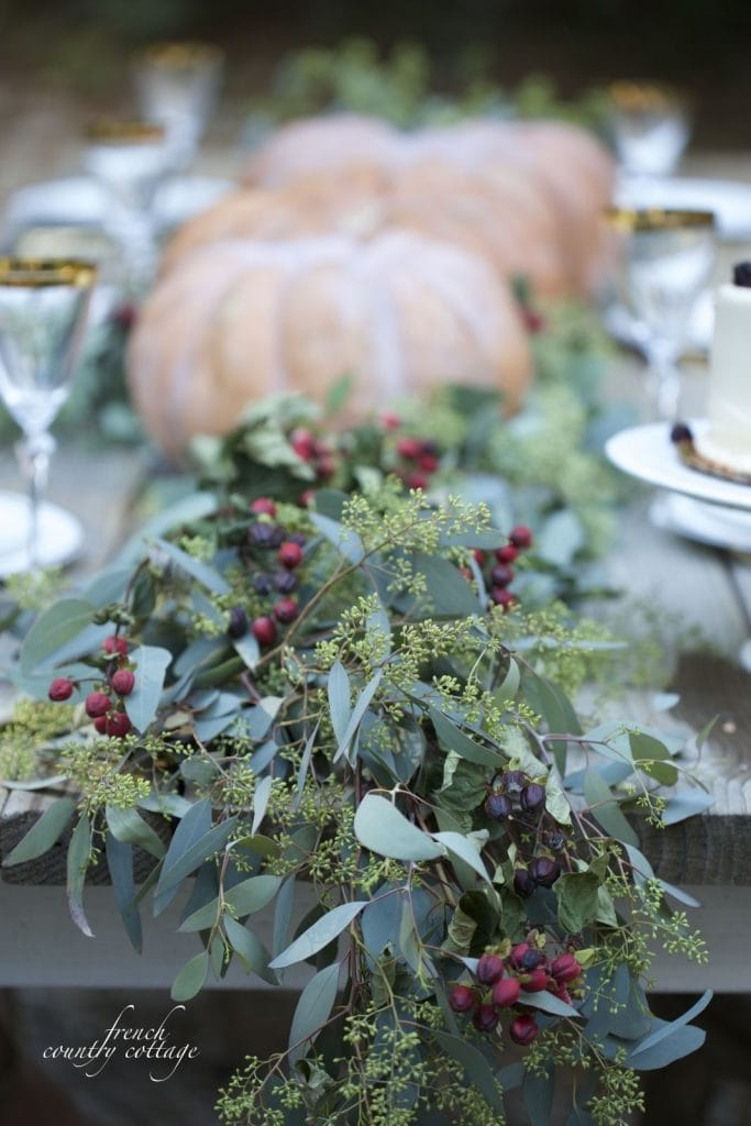 dramatic Thanksgiving table setting with pumpkins and eucalyptus garland and berries