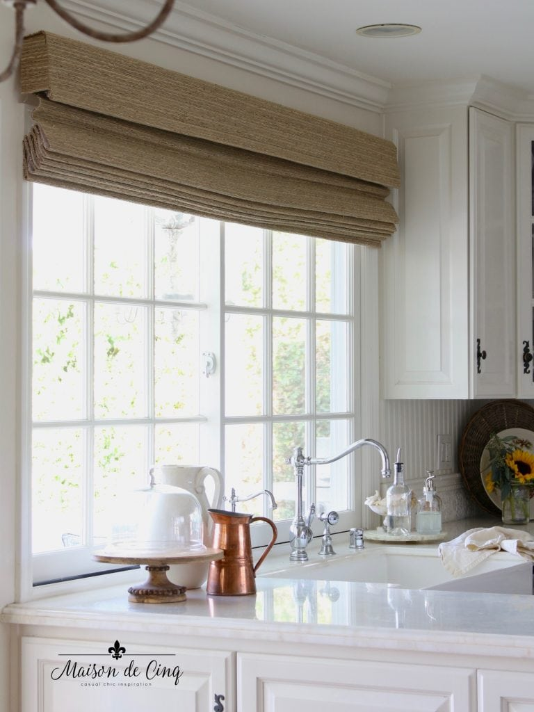woven wood blinds in natural seagrass color in white farmhouse kitchen