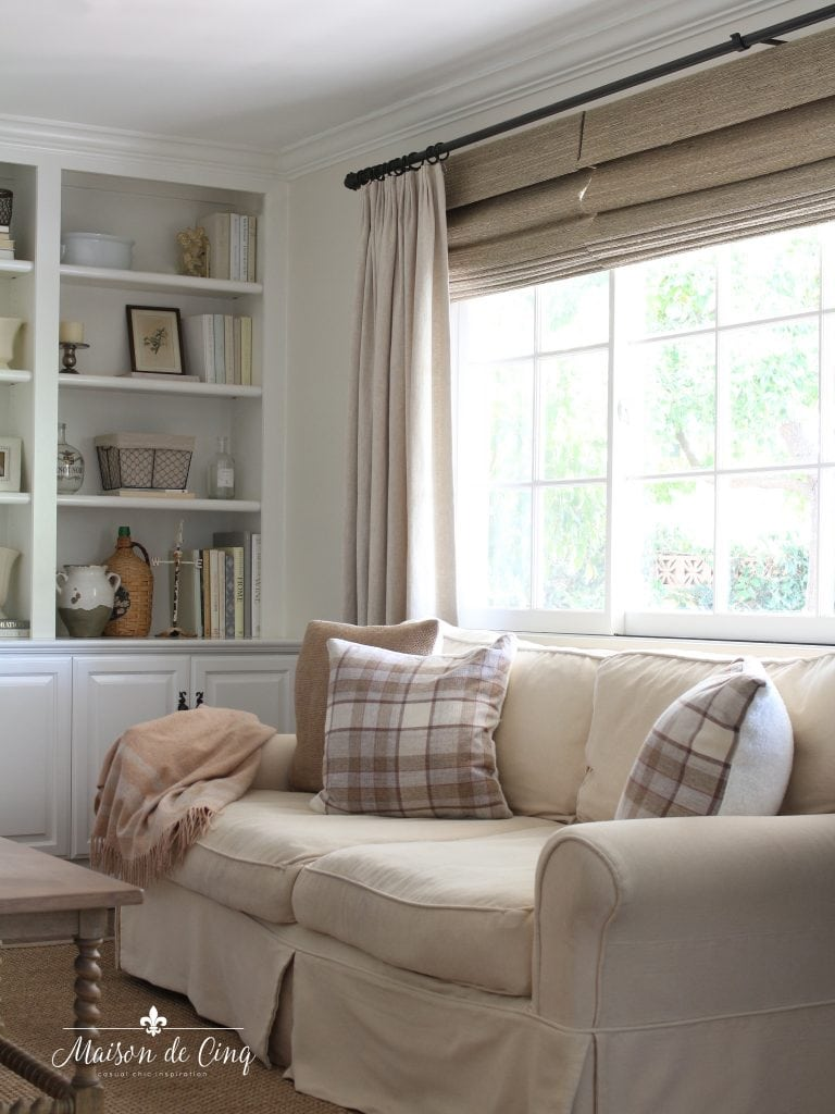 neutral French farmhouse family room with woven wood shades and linen drapes