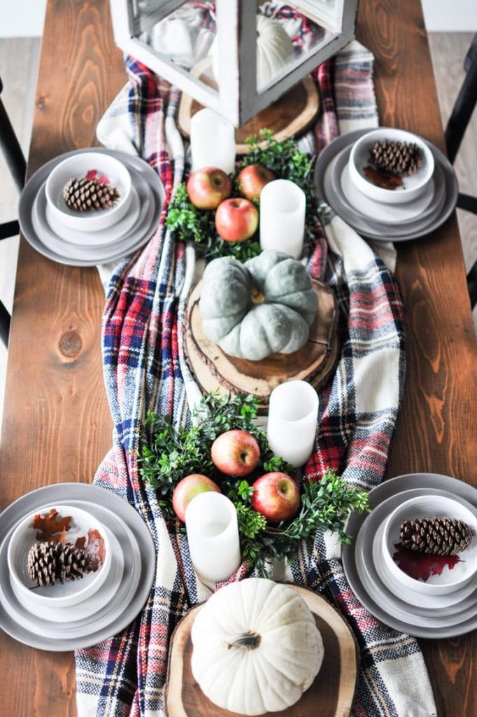 fall tablescape with plaid runner pinecones and pumpkins