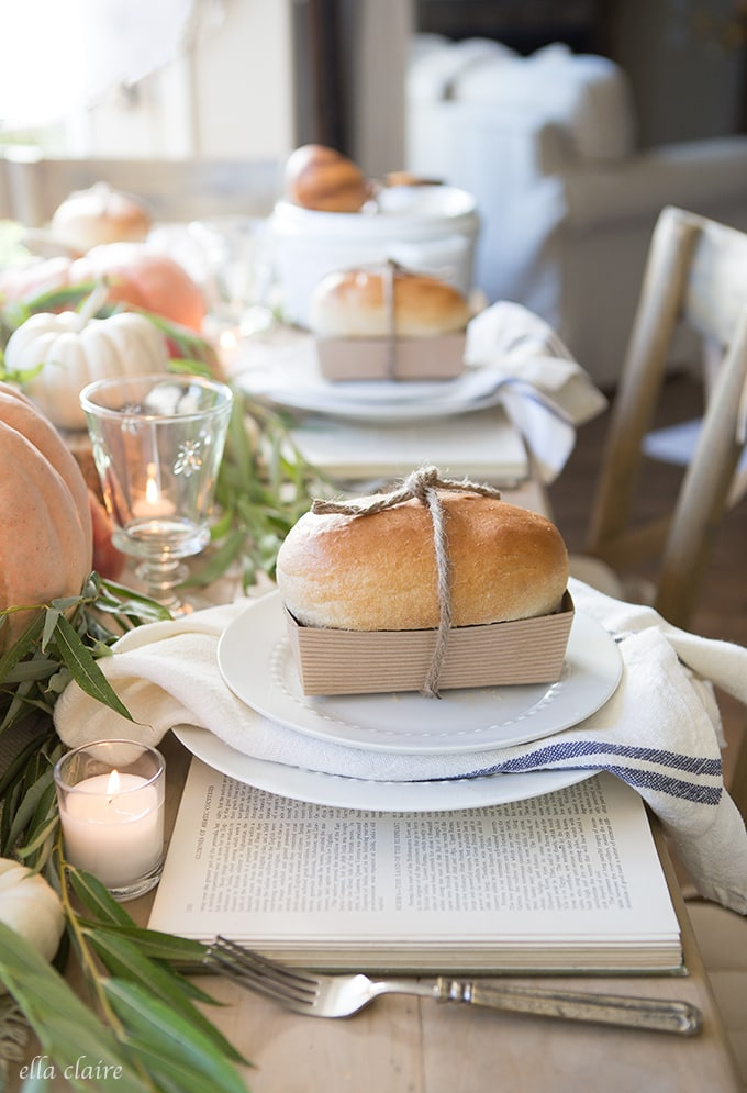 cute fall table with bread loaves on plates and pumpkins