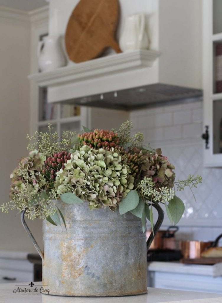 gorgeous hydrangeas in a vintage bucket in white french country kitchen fall decorating ideas