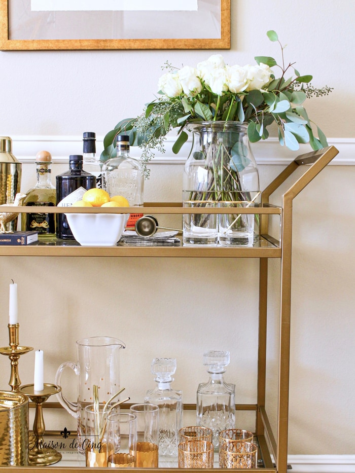 gorgeous bar cart styling on brass gold bar cart with bar accessories and flowers